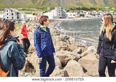 four friends women tourists walking near the sea bay in Iceland