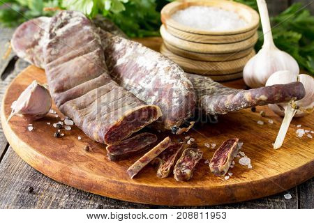 Beef Jerky Smoked Sausage Sudzhuk With Spices And Garlic Is Served On A Cutting Board.
