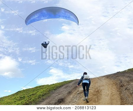 A young woman with a backpack behind her shoulders climbs up a mountain and looks at the floating paraglider hovering in the air against the blue sky and white clouds