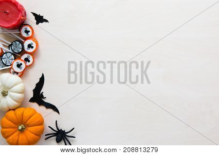 Halloween holiday background with spiders bats candies and pumpkins on wooden background top view