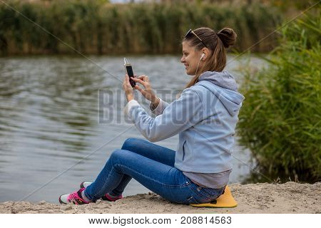 Young woman in excellent spirits sits on the river bank uses a phone and listens to music on headphones