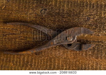 Dirty set of hand old rusty pliers tools on a wooden background. Equipment for locksmith and metalworking shop