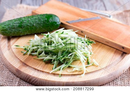 Green cucumber grated on wooden board on the table