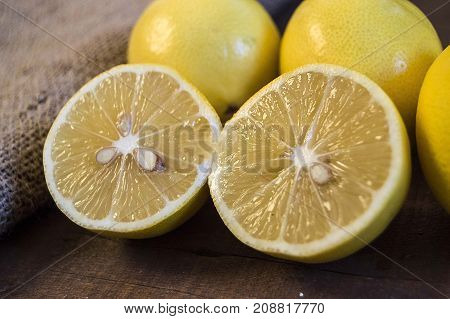 Photos of lemon with knife on wooden floors, hand-cut half a lemon. dividing a lemon into two equal parts, cutting fresh lemon with a knife,