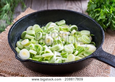 Stewing leek slices in a frying pan on a hot plate
