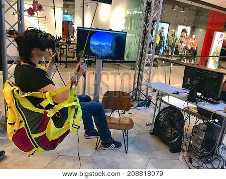 Stuttgart, Germany - October 14, 2017: A girl is expering a virtual paragliding ride wearing virtual reality goggles by HTC Vive and controllers during a presentation in a shopping mall.