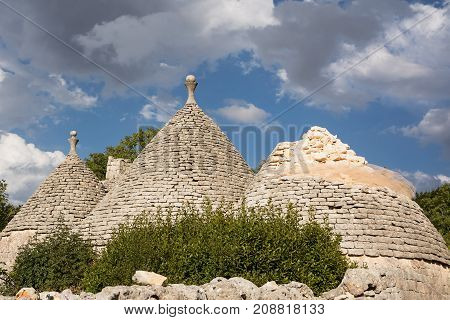 Old trulli of which one collapsed and cloudy sky
