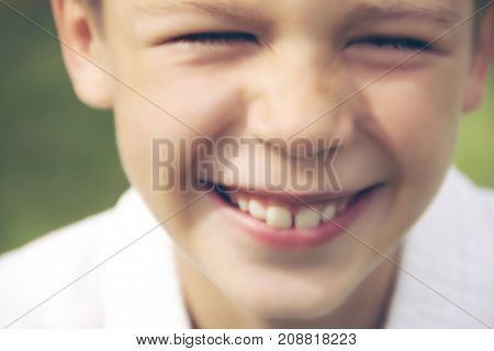 Blurred (defocusing) picture for background of smiling teenager boy on a green background.Toning