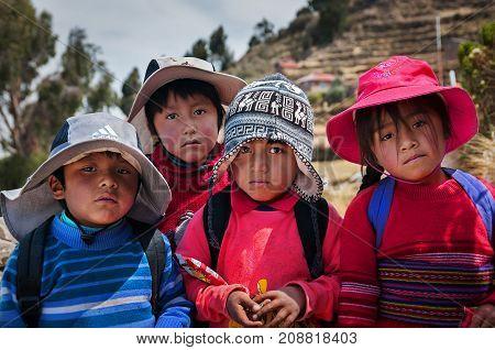 TAQUILE ISLAND, PUNO, PERU - OCTOBER 13, 2016: Close up portrait of peruvian children. Latin Americans .