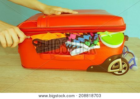 Woman hands putting clothes in suitcase closeup. Travel and vacations concept. Suitcase with different things prepared for travel - Retro color