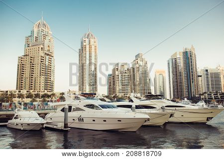 Luxury yachts parked on the pier in Dubai Marina bay with city view