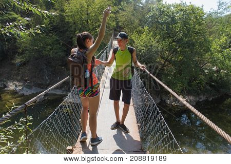 Travelers travel on the suspension bridge go trekking together. Active hikers. Trekking together. Eco tourism and healthy lifestyle concept. Two young Tourists With Backpacks travel