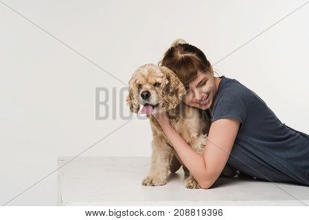 Young woman hugging her american cocker spaniel on white background