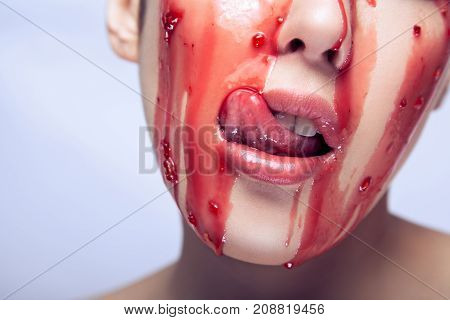 Closeup. Detail Shot Of Beautiful Woman, Open Mouth And Touching Tongue Red Jam Is Flowing In The Fa