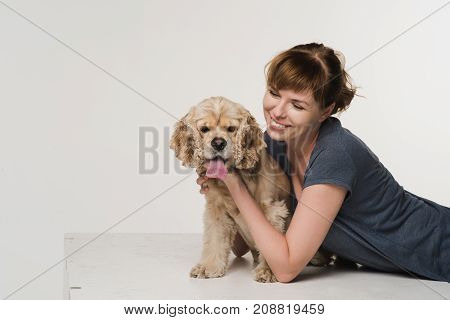 Young woman hugging her american cocker spaniel on white background. A girl looks at her dog.