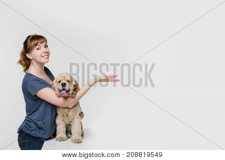 A woman with her american cocker spaniel pointing to space at right with hand isolated on white background. Pointing with the palm of his hand and looking at the camera