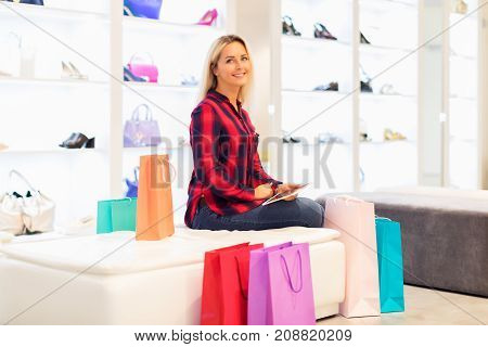 Young blonde smiling attractive woman with long hair using a tablet computer PC in the fashion wear store with color shopping bags