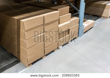 Carton boxes on concrete floor with metal beam construction in storage