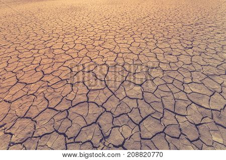 Land is covered with cracks as a symbol of drought extreme weather conditions or as a background. Toned image