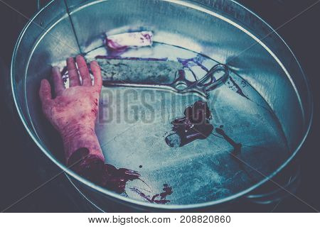 Hand amputated by a medical saw as an illustration of the work of doctors during the war or illegal activities of surgeons or crime scene. Toned image