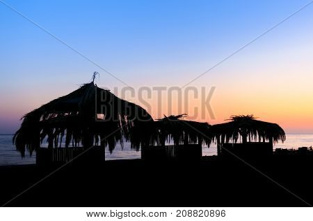 Silhouettes of wooden hovels covered with reeds and palm leaves on the beach at sunset