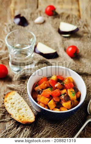 Eggplant potato Bell pepper goulash on a wood background