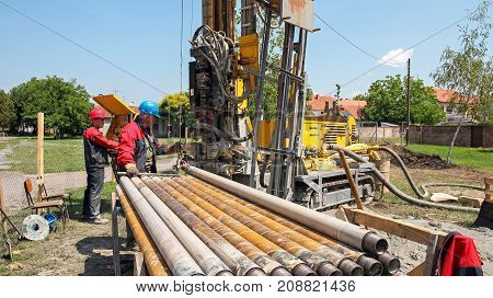 Drilling geothermal well for a residential geothermal heat pump. Workers on Drilling Rig.