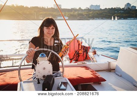 Young pretty smiling woman in black shirt and striped skirt driving luxury yacht at sea, sunset.