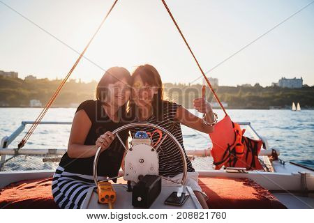 Two young pretty smiling girls, friends driving luxury yacht in sea, summer sunset.
