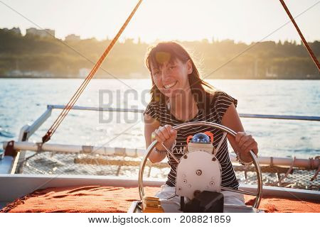 Young pretty smiling woman in striped shirt and white shorts driving luxury yacht in sea, sunset.
