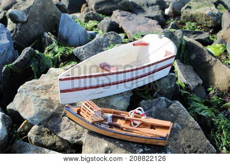 Two toy wooden boats sitting on the rocky shoreline.