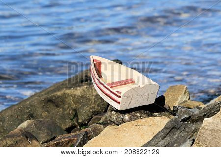 Small wooden toy boat sitting on rocky shoreline.