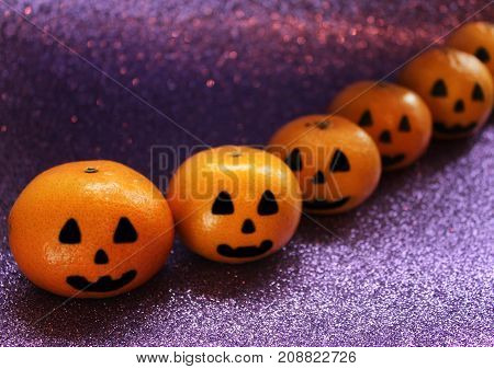 Orange mandarins in the form of a pumpkin painted in the form of icons of Halloween on the brilliant purple background closeup.