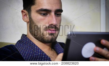 Handsome young man at home reading with tablet PC lying on couch at night, wearing night-gown