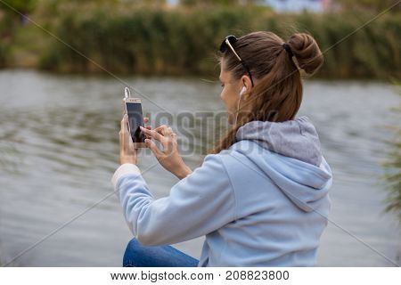 Young smiling woman in excellent spirits sits on the river bank with a phone and listens to music on headphones
