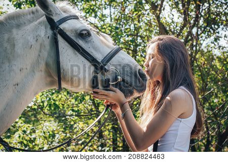 Girl teenager and white horse in a park in a summer day