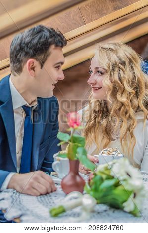 Just married couple looks at each other in the cafe