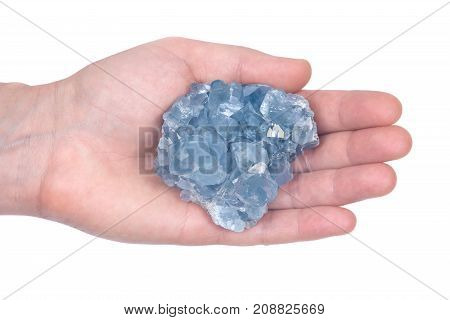 Woman's hand holding blue celestite cluster isolated on white background