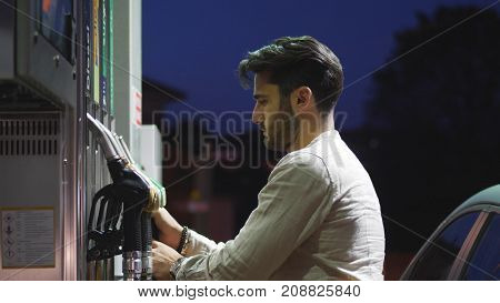 Young man fueling his car at gas station, using the pump nozzle. Late at night
