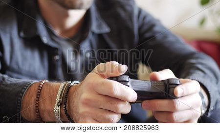 Attractive young man using joystick or joypad for videogames, sitting on couch at home in his living room, staring at TV screen