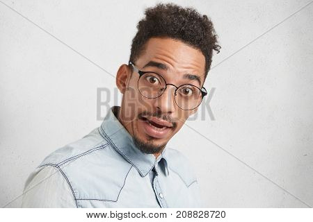Is It Really So? Surprised Mixed Race Male Nerd Looks In Bewilderment At Camera, Wears Round Spectac