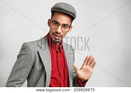 Handsome Man Wears Round Spectacles, Wears Old Fashioned Clothes, Shows Palm, Tries To Stop Somethin