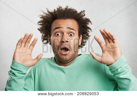 Headshot Of Young Mixed Race Man With Afro Hairstyle, Has Stunned Fearful Expression, Raises Palms A
