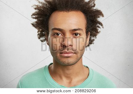 Portrait Of Dark Skinned Confident Man With Curly Afro Hairstyle Has Calm Face Expression, Looks Dir