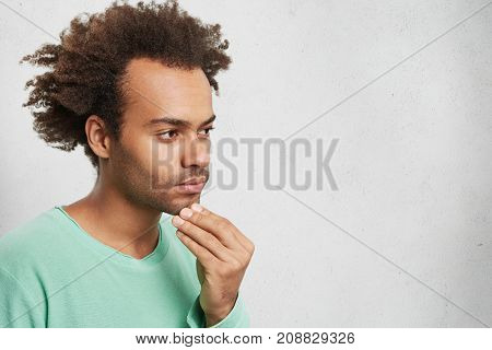 Horizontal Portrait Of Pensive Mixed Race Man With Afro Hairstyle, Keeps Hand On Chin, Has Some Trou