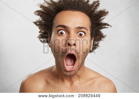 Headshot Of Dark Skinned Handsome Guy With Afro Hairstyle Stares At Camera With Bugged Eyes And Wide