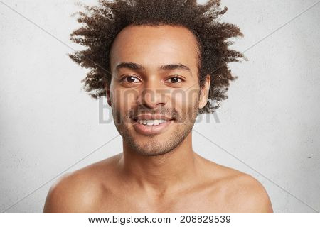 Naked Positive Afro American Male With Dark Healthy Skin And Curly Hair, Smiles Gently As Being Glad