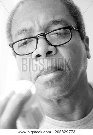 African american male taking his blood pressure medication at home.