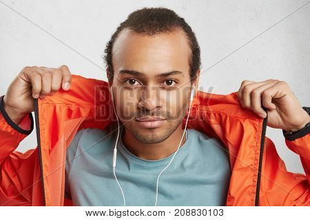 Stylish Attractive Male Model With Bristle, Listens To Music Uses Earphones, Keeps Hands On Orange A