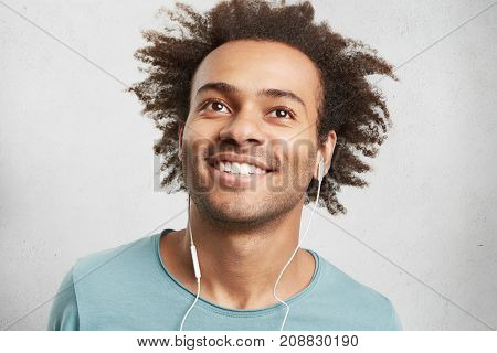 Portrait Of Cool Young Black Man With Curly Hair, Has Cheerful Expression, Smiles Broadly, Demonstra